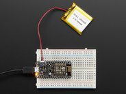 Adafruit Feather HUZZAH with ESP8266 WiFi shown on breadboard with battery pack (not included)
