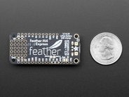 Adafruit Feather M4 shown with quarter for scale